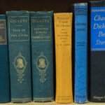 six Charles Dickens books in green, blue and yellow